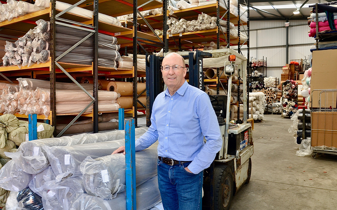 Mike Donohue (Managing Director) Standing in Warehouse With Fabric